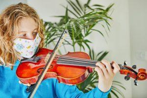 Girl wearing mask plays violin